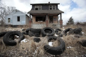 Ilegally dumped tires sit in front of a vacant, blighted home in a once thriving neighborhood on the east side of Detroit